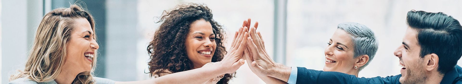 Smiling employees giving each other a high-five in the office
